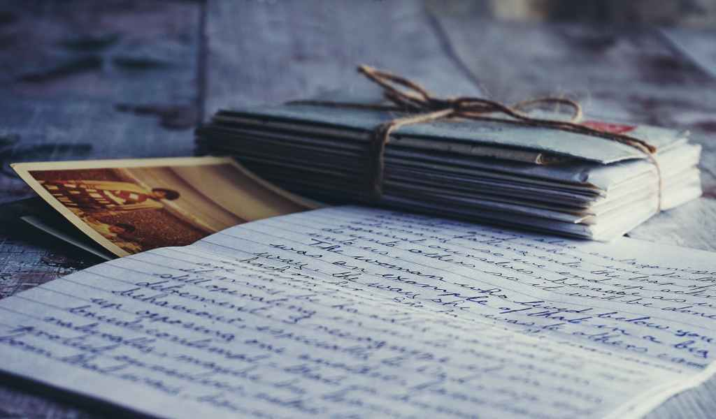 stack of letters tied with twine, a couple postcards, and a handwritten letter