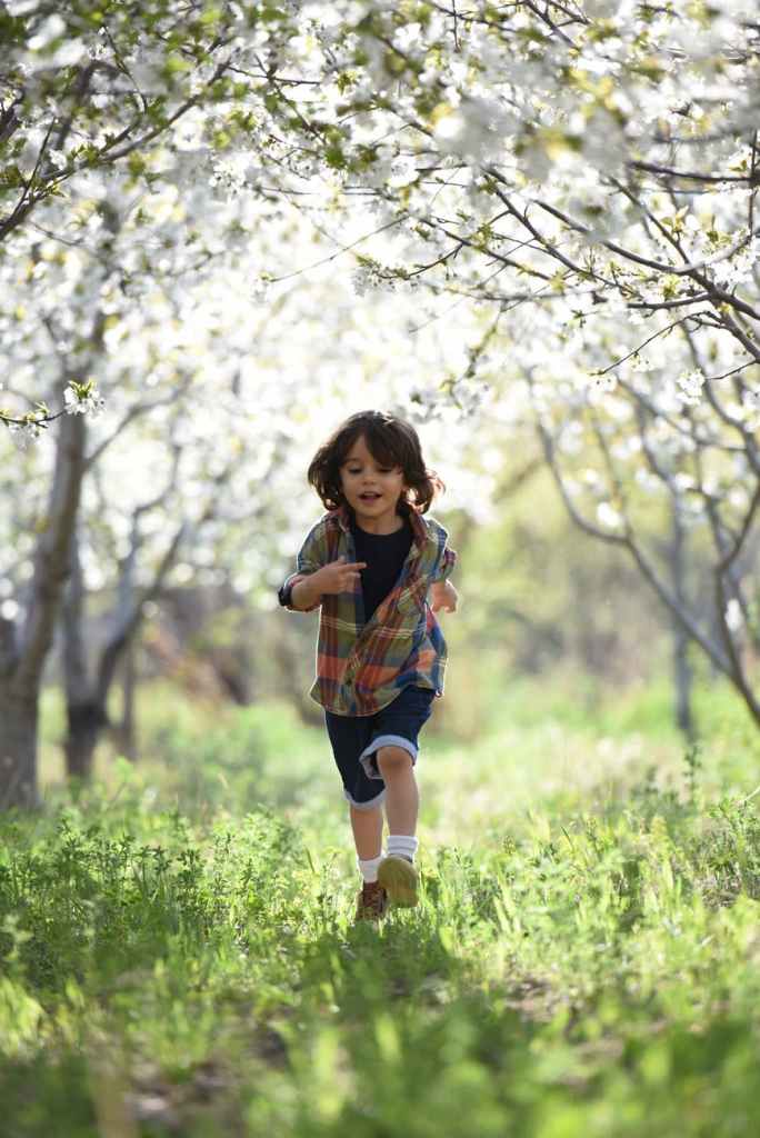 A young boy running through a field, with trees surrounding